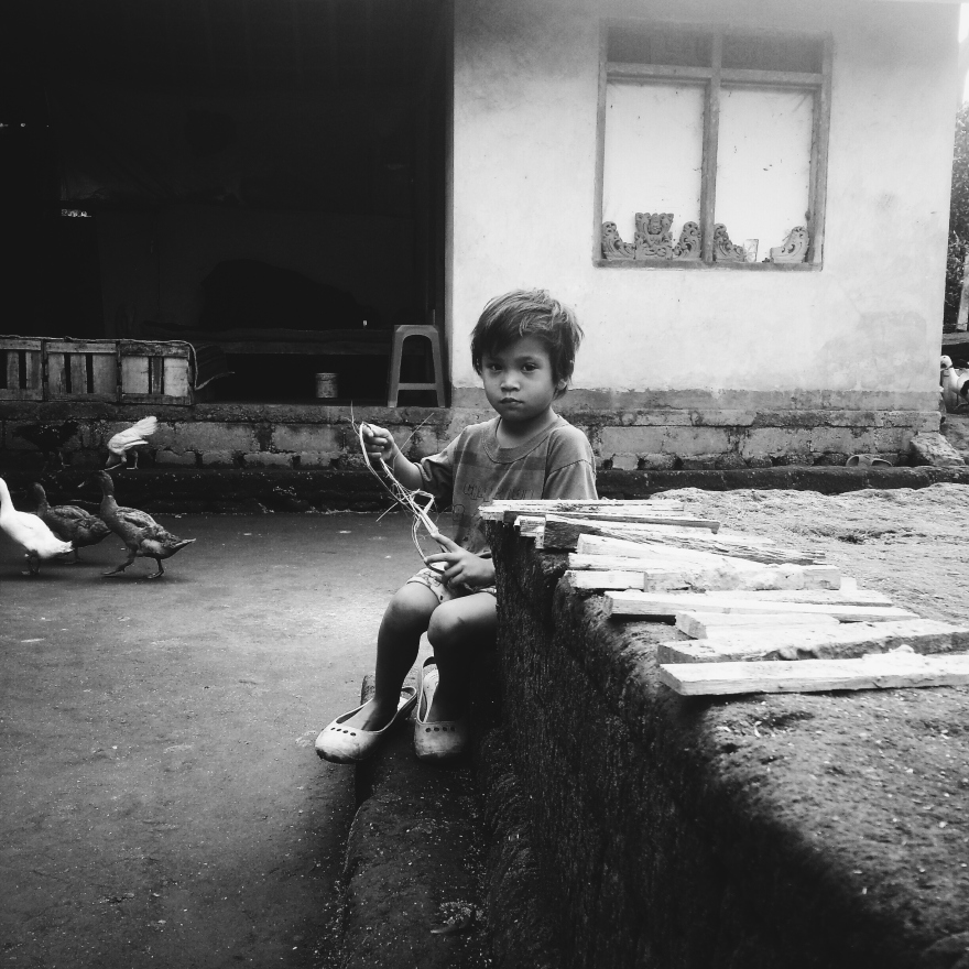 A child playing with planks of wood in the Balinese house